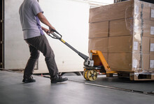 Warehouse Worker Unloading Cargo Pallet Out Of The Inside Container Truck. Shipment Boxes. Delivery Service.