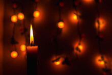 Close-up Of Burning Candle Against Wall