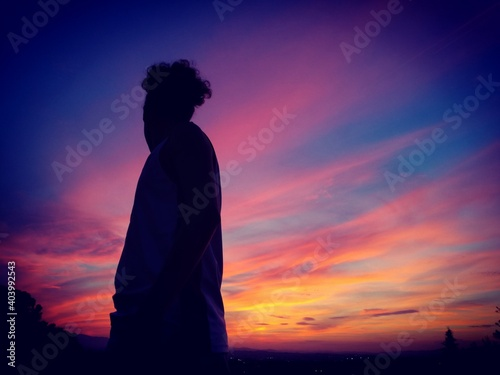 Low Angle View Of Man Standing Against Cloudy Sky At Dusk
