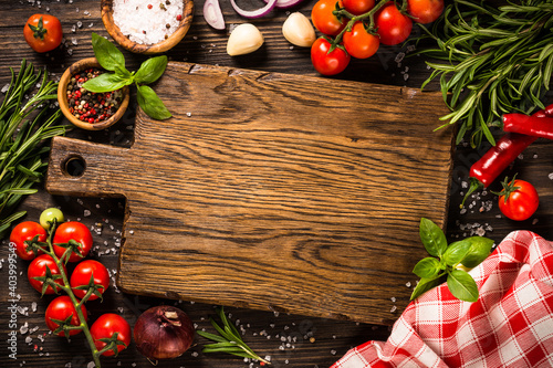Fototapeta Food cooking background with cutting board, spices, herbs and vegetables at wooden kitchen table. Top view with copy space. obraz