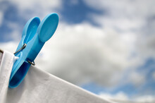 Close Up Of Blue Peg And White Fabric On A Clothesline