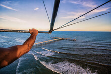 Cropped Hand Of Man Flying With Hang Glider Over Sea