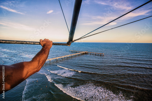 Photo Cropped Hand Of Man Flying With Hang Glider Over Sea