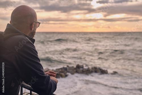 Obraz na plátně Un giovane ragazzo sta ammirando il meraviglioso tramonto sul mare da Riomaggior