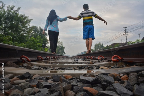 Obraz Surface Level View Of Couple Holding Hands While Walking On Railroad Track - fototapety do salonu