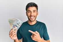 Young Handsome Man Holding Dollars Smiling Happy Pointing With Hand And Finger