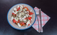"Greek ""dakos"" Cretan Salad With Tomatoes, Feta And Rye Rusks, Healthy Mediterranean Food On Black Background"
