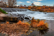 Autumn Landscape. Streams Of Water, Shot With Long Exposure, Fall On A Man-made Dam. Autumn Man-made Waterfall Landscape
