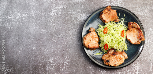Photo Pork loin chops with cabbage slaw on a round plate on a dark background