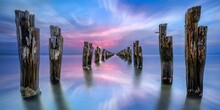 Wooden Posts In Sea Against Dramatic Sky At Sunset