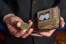 A Man In A Suit Holds A Bitcoin In His Hand. Men's Hands Take Out Or Put A Bill In A Wallet.
