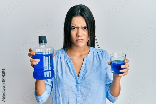 Fototapeta Young hispanic girl holding mouthwash for fresh breath skeptic and nervous, frowning upset because of problem