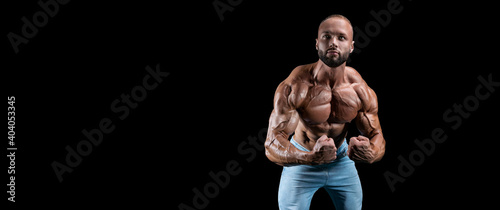 Isolated muscular man on a black background Fototapet