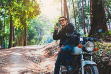 A Young Male Traveler Traveling On A Motorbike Is Talking On The Phone With A Friend.