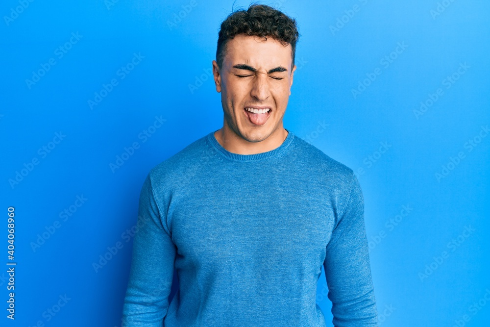 Fototapeta Hispanic young man wearing casual winter sweater sticking tongue out happy with funny expression. emotion concept.