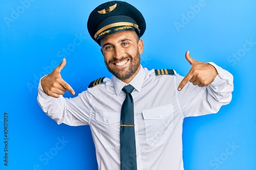 Tableau sur Toile Handsome man with beard wearing airplane pilot uniform looking confident with smile on face, pointing oneself with fingers proud and happy