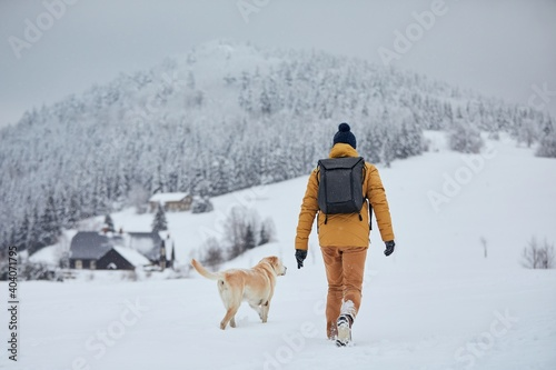 Obraz Rear view of young man with dog in winter. Pet owner with his labrador retriever walking against old village in beautiful nature. Jizera mountains, Czech Republic - fototapety do salonu