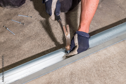 Obraz na plátně View of male worker hammering dowel nails in metal rail