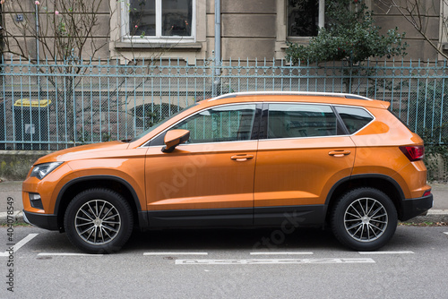 Mulhouse - France - 9 January 2021 - Profile view of Orange Seat Ateca, the famous spanish SUV car parked in the street