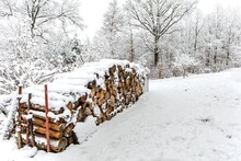 Snow Covered Firewood Stack At Winter. Winter Village Landscape. Stacked Wood Covered With Snow. Background. A Woodpile Of Dry Fire Woods In The Winter.