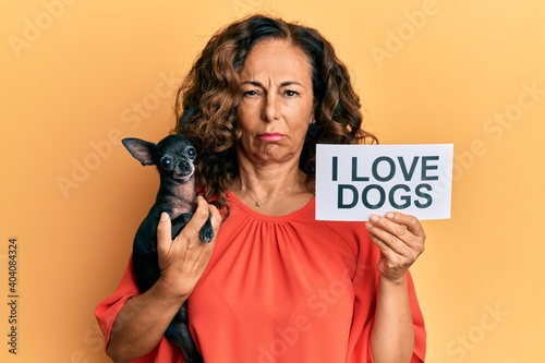 Fototapeta Middle age hispanic woman holding chihuahua dog and paper with i love dogs phrase skeptic and nervous, frowning upset because of problem