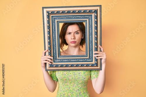 Fotografie, Obraz Young beautiful woman holding empty frame skeptic and nervous, frowning upset because of problem