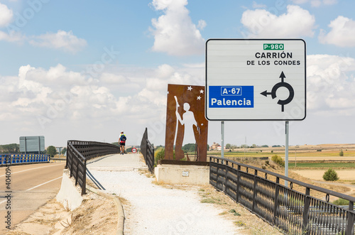 a pilgrim walking a gravel road in direction to Carrion de los Condes next to Fromista, province of Palencia, Castile and Leon, Spain