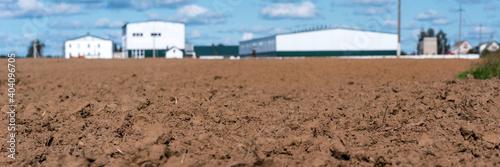 Fotografie, Obraz Agronomy tillage field with brown soil against white building of farm land