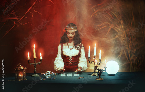 Fotografia Fantasy girl in image of gypsy witch sits at table in dark gothic room