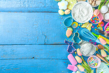 Easter Baking Background With Rolling Pin, Whisk, Eggs, Flour And Colorful Sugar Confetti On Blue Wooden Table Top View. Flat Lay With Copy Space For Text