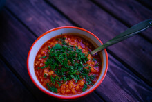 Lentil Soup With Greens In An Orange Bowl On A Wooden Background