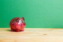 Close-up Of Piggy Bank On Wooden Table Against Green Wall