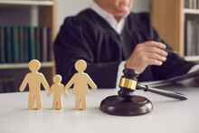 Gavel, Sound Block And Small Wooden Figurines Of Husband, Wife And Kid On Judge's Table In Courthouse During Court Hearing. Family Law, Divorce Lawyer, Joint Custody Of Child And Alimony Concept