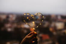 Hand Holding Heart Made Of Fairy Lights On Window Background.