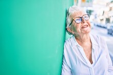 Elder Senior Woman With Grey Hair Smiling Happy Leaning On The Wall Outdoors