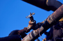 Rusty Water Tap On Blue Sky Background