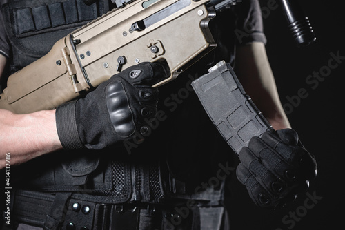 Fotografie, Obraz Soldier is reloading the rifle close up concept.