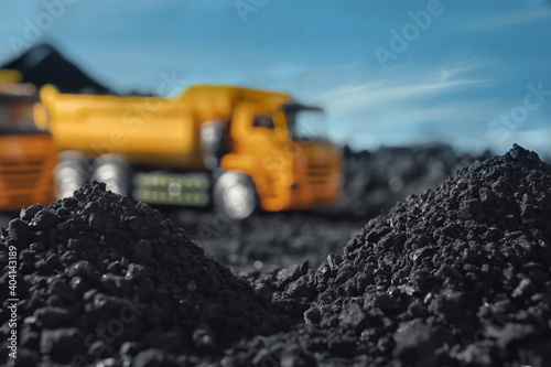 Pile of coal and blurred yellow truck on background, closeup Fotobehang