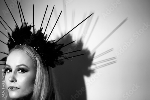 Fashion portrait of beautiful young model with professional makeup, perfect skin and Halo crown on her head.