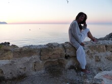 Young Woman Sitting On Stone Wall By Sea Against Sky During Sunset