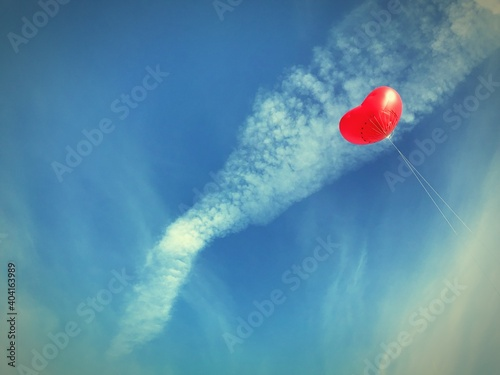 Low Angle View Of Heart Shape Balloon Flying Against Cloudy Sky