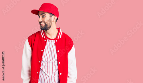 Fotografie, Obraz Young handsome man with beard wearing baseball jacket and cap looking away to side with smile on face, natural expression
