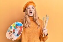 Beautiful Young Caucasian Girl Holding Paintbrush And Painter Palette Angry And Mad Screaming Frustrated And Furious, Shouting With Anger Looking Up.