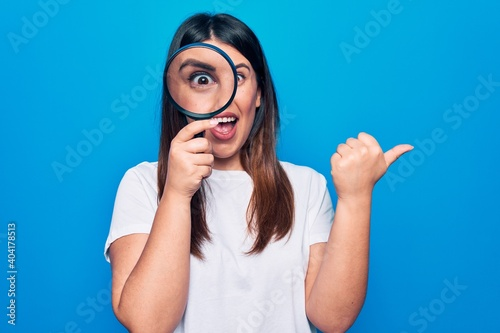 Fototapeta Young beautiful brunette woman using magnifying glass over isolated blue backgro