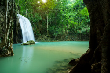 waterfall clear emerald water or blue pool with spa fish on summer season with rock and tree roots for holiday relax travel in green jungle or forest at erawan waterfall floor 3 for nature landscape