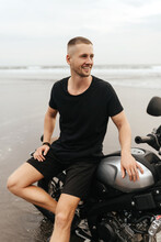 Close Up Portrait Of Biker At Beach Of Bali Indonesia. Handsome Man Sitting On Handmade Vintage Recast Motorcycle