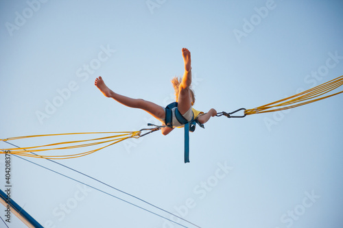 Obraz A little cheerful girl flies on springy bright elastic bands and jumps on a trampoline enjoying the long-awaited vacation in the warm sun - fototapety do salonu