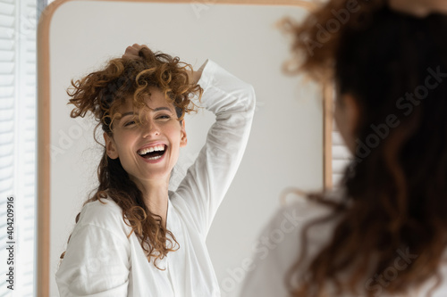 Valokuva Overjoyed young Caucasian woman look in mirror at home bathroom have fun getting ready