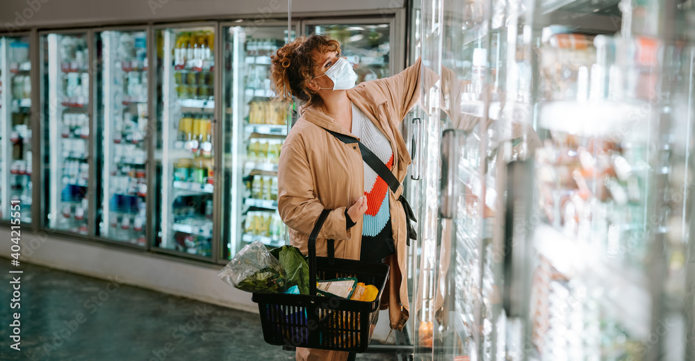 Fototapeta Woman with face mask shopping groceries in supermarket