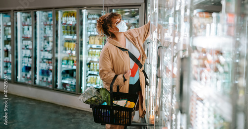 Obraz na plátně Woman with face mask shopping groceries in supermarket